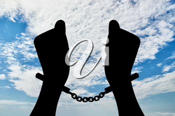 Freedom concept. Silhouette of human hands in handcuffs against the sky