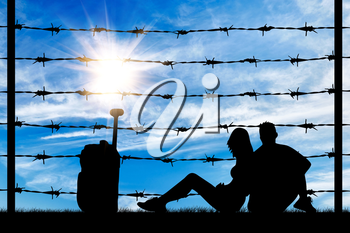 Concept of refugee. Silhouette starving refugee families with a bag near the fence of barbed wire