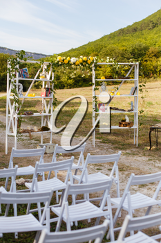 Happy outdoor Wedding Ceremony Scene for a summer mountain wedding. Wedding aisle, decorated wedding alter and flower decorations with mountains in the background. Wedding color pear