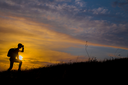 Follow your dreams, silhouette of man at sunset. Hiker with backpack walking in the field. Over sunset. Summer healthy active lifestyle. Single travel.