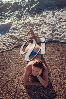 Young beautiful smiling woman with red hair in blue and pink swimsuit is sitting on the beach of caribbean sea with at sunset