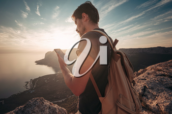 Man backpacker using smartphone relaxing on mountain top traveling alone. lifestyle active vacations modern technology millennials concept. Marvelous daybreak. mock up text.