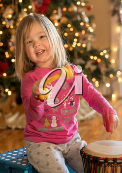 Young toddler girl playing an african drum with pieces of rope in front of christmas tree