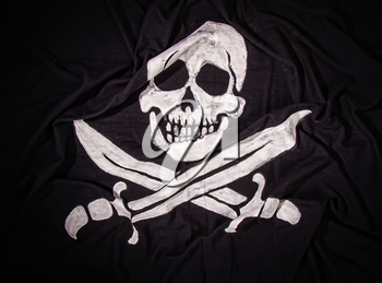 traditional waving pirate flag jolly roger skull with two crossed sabers on dark fabric background