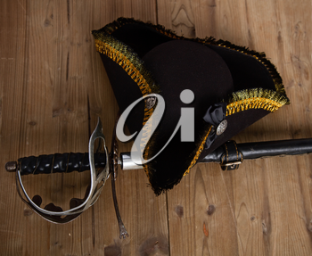 Classic pirate black felt captain's cocked hat and scabbard sword lying on a wooden background