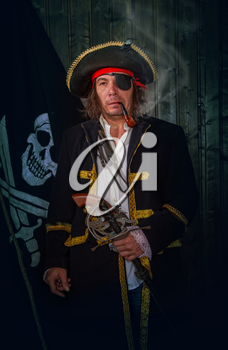 Adult pirate captain in a traditional costume and with a weapon smokes a pipe against the background of a jolly roger