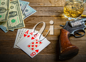 playing cards laid out on an old wooden table in the saloon money, whiskey and a revolver for self-defense