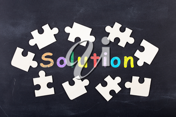 Business Solution concept - inscription and jigsaw blocks on the blackboard