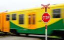 Fast move yellow regional train pass by railroad crossing.