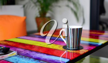 Multicolor glass table with cup of coffee in modern furnished living room. Focused on foreground with cup of coffee.