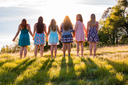 Young Girls Standing Together in Grassy Field Facing the Bright Sunset