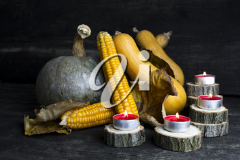 Pumpkin, Corncob, autumn leaves and burning candles Decoration on a wooden table