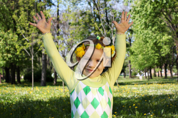 happy little girl in park with hand up