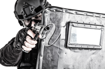 Police quick reaction team, special operations tactical group member in mask, helmet and goggles, hiding behind ballistic shield, aiming with pistol in firefight with dangerous criminals or terrorists