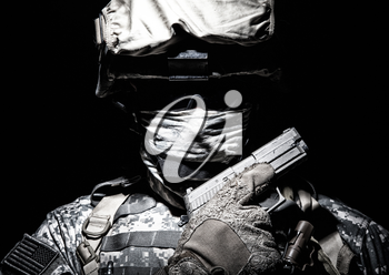 Special operations forces soldier in combat helmet with hidden behind balaclava and dark glasses face posing with sidearm service pistol in hand. Brown tone, high contrast, cropped on black background