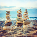 Three stacks of round smooth stones on the beach