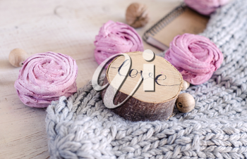 Homemade pink berry marshmallow. Composition with the inscription Love, wooden and knitted elements.
