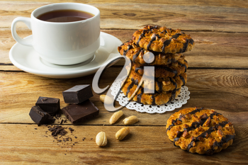 Chocolate icing cookies with peanuts and cup of tea on a rustic wooden table. Breakfast biscuits and tea.
