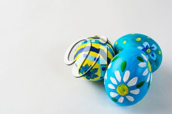 Blue hand-painted Easter eggs with floral design on a white background. Easter background. Easter symbol. Copy space