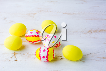 Decorated Easter white pink red yellow eggs on a white wooden background, space for text, copy space