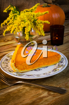 Pumpkin pie slice on the rustic  wooden table. Traditional Thanksgiving pumpkin pastry. Squash pie slice.