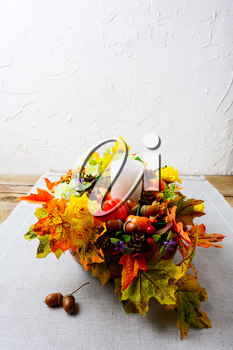 Thanksgiving decoration with silk fall leaves on linen napkin, vertical. Thanksgiving greeting with fall decor. Fall centerpiece. Thanksgiving background. Copy space.