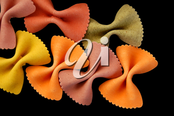 Multi colored farfalle bow ties pasta against a black backgrround.