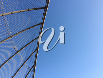 Geometric design element chain link baseball backstop fence and blue sky