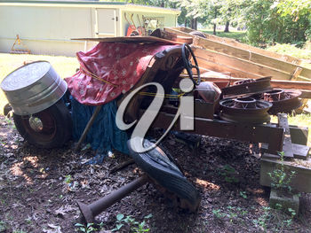 rusty antique ford car in backyard with spoked wheels junkyard