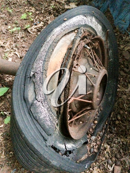 rusty antique ford car parts in backyard with spoked wheels junkyard