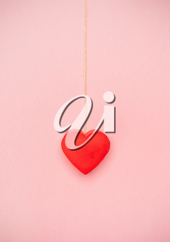 Heart hanging to a string of twine on pink background. Love concept hanging by a thread.
