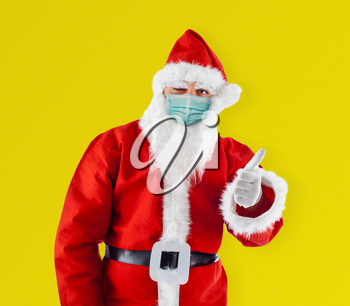 Santa Claus Santa Claus with surgical mask shows thumb up shows thumb up on yellow background.