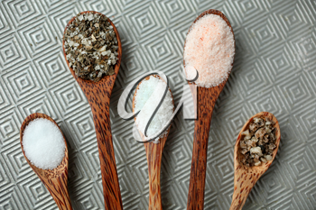 five different kind of salt in a wooden spoon on textured background